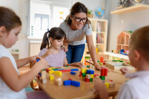 Preschool teacher with children playing with didactic toys