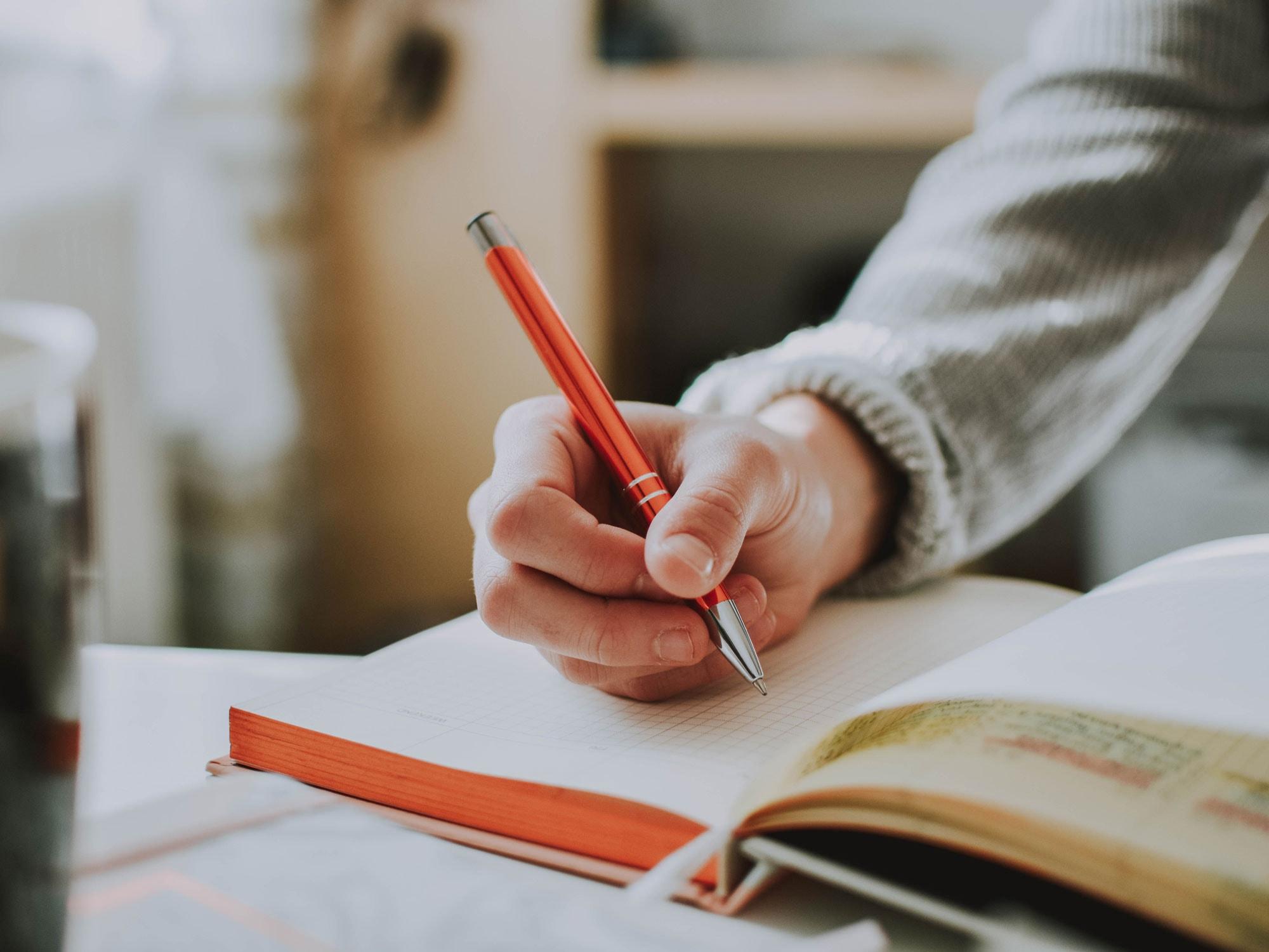 person-holding-orange-pen-1925536